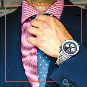 Man fixing his tie wearing a very nice watch